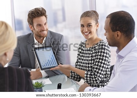 Beautiful young businesswoman using tablet computer at a business meeting, smiling happy.