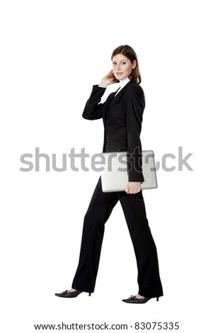 Beautiful young businesswoman walking and holding notebook in her hand - stock photo