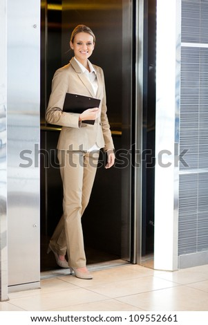 beautiful young businesswoman walking out elevator - stock photo