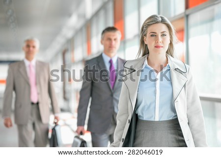 Beautiful young businesswoman walking with male colleagues in background at train platform - stock photo