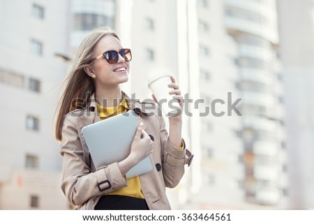 Beautiful young businesswoman with a disposable coffee cup, drinking coffee, and holding tablet in her hands against urban city background. - stock photo