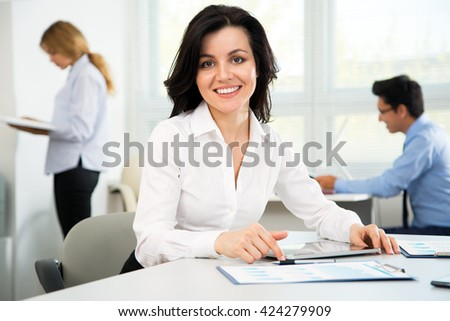 Beautiful young businesswoman with colleagues discussing in the background
