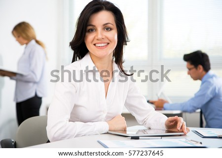Beautiful young businesswoman with colleagues in modern office