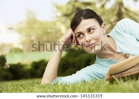 Beautiful young businesswoman with newspaper looking away while lying on grass at park - stock photo