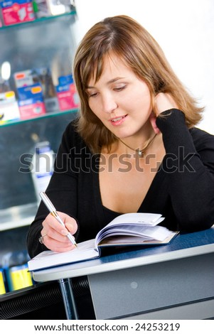 Beautiful young businesswoman writing down paperwork