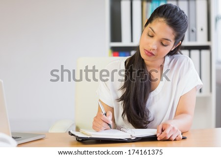 Beautiful young businesswoman writing in diary at office desk