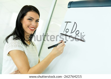Beautiful, young, businesswoman writing To Do onto a white writing board - stock photo