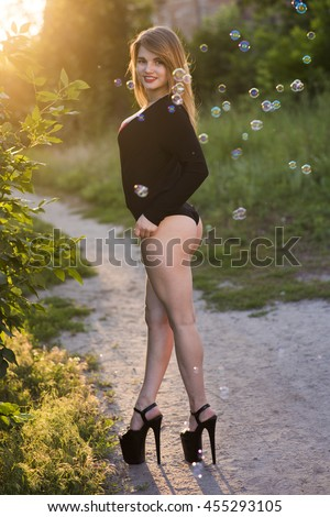 Beautiful young busty lady posing in stylish black swimsuit and high heels outdoors - stock photo
