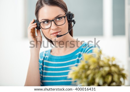 big beautiful modern office photo. beautiful young call center operator in modern office with big window woman wearing glasses and photo