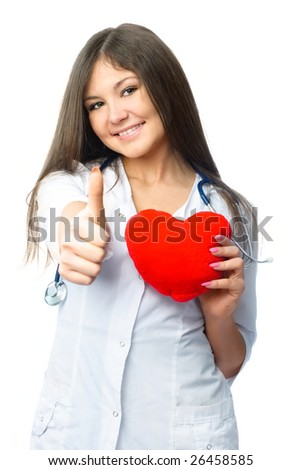 beautiful young cardiologist with a heart shaped pillow and her thumb up - stock photo