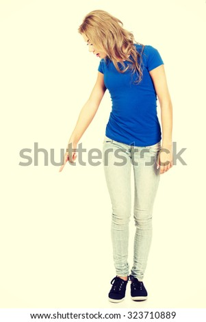 Beautiful young casual woman pointing down. - stock photo