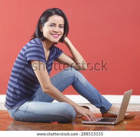 Beautiful young casual woman smiling sitting on the floor with her computer - stock photo