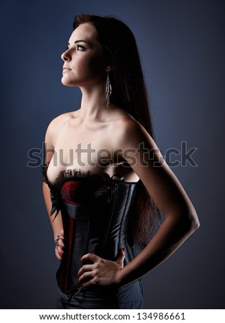 Beautiful young caucasian adult woman in a red and black silk corset against a light blue background - stock photo