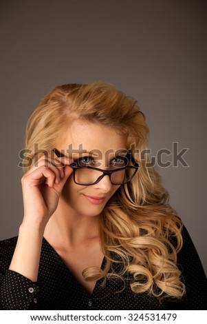 Beautiful young caucasian blond woman with eye glasses looking into copy space - stock photo
