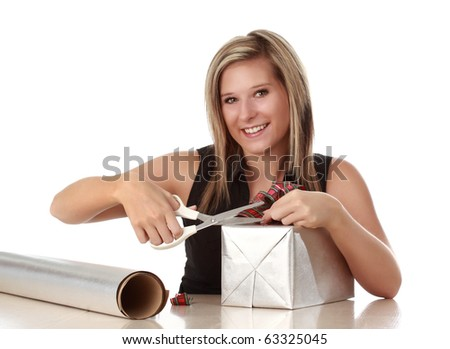 beautiful young caucasian blond woman wrapping christmas gift, isolated on white background - stock photo