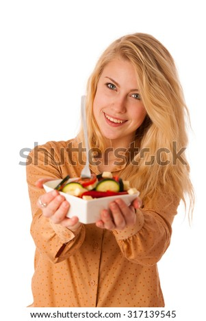 Beautiful young caucasian blonde woman eats a delicious  salad as a sign for healthy eating isolated over white
