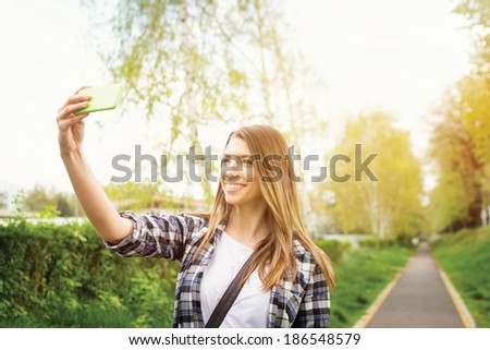 Beautiful young Caucasian blonde woman taking a selfie photo with smart phone outdoors on sunny summer day. Modern young people lifestyle. Teenage student girl photographing herself. - stock photo