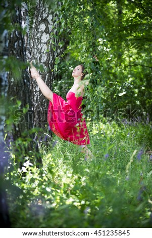 Beautiful young caucasian brunette woman in red dress outdoors, whole-length portrait, flexibility and stretching on nature - stock photo