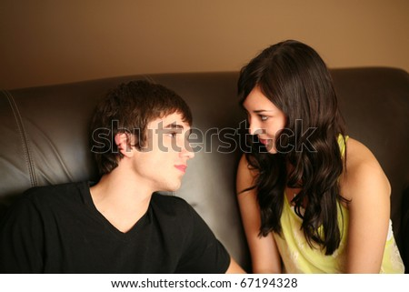 beautiful young caucasian couple looking into each others eyes - stock photo