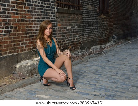 Beautiful young Caucasian female model poses in cobblestoned alley wearing a blue-green romper - stock photo