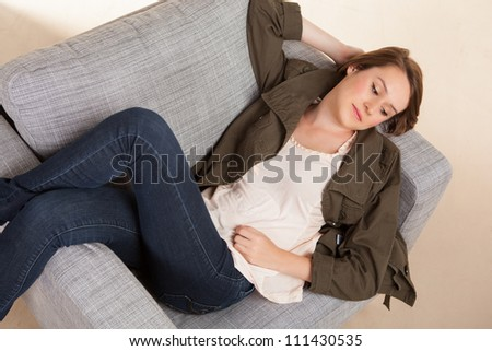 Beautiful young Caucasian female relaxing on grey chair at home with long brown hair.