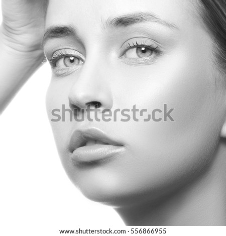 Beautiful young caucasian girl with green eyes, natural lips, makeup and blonde hair looking at camera. Woman portrait. Black and white