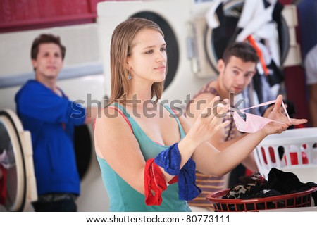 Beautiful young Caucasian lady folds underwear in the laundromat - stock photo