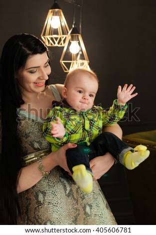 Beautiful young caucasian mother holding her little baby son in her arms in the stylish studio on a background of light bulbs in a modernist style, cuddle her son. minimalism, interior, low key - stock photo