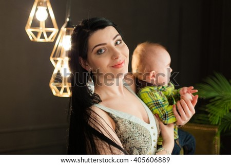 Beautiful young caucasian mother holding her little baby son in her arms in the stylish studio on a background of light bulbs in a modernist style, cuddle her son. minimalism, low key, closeup - stock photo