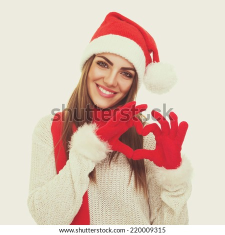 Beautiful young Caucasian Santa Claus woman gesturing heart. Cute young teenage girl with knitted hat and red scarf and gloves showing heart smiling. Instant filter. Square format image. - stock photo
