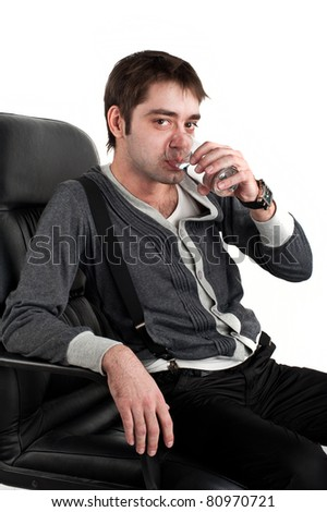 Beautiful young caucasian white guy sitting on a black leather chair and with a calm expression on his face holding a glass of water on top of an isolated white - stock photo