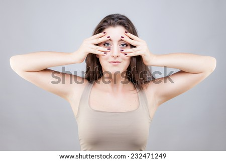 Beautiful young caucasian woman doing face yoga pose - stock photo