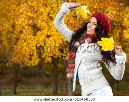 beautiful young caucasian woman in warm red colorful clothing  on yellow maple leaves outdoors smiling happy