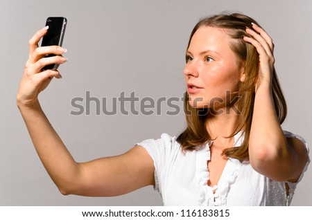 beautiful young caucasian woman on gray background is talking photos of herself - stock photo