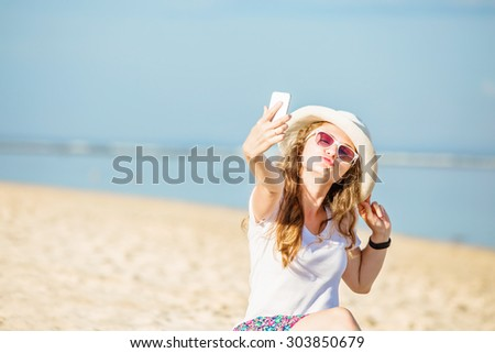 Beautiful young caucasian woman on the beach in white hat taking selfie picture with mobile phone. Sunny day on summer vacation - stock photo