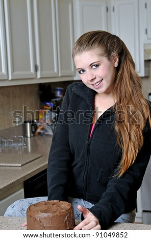 Beautiful young Caucasian woman relaxing in kitchen smiling in front of chocolate cake. - stock photo
