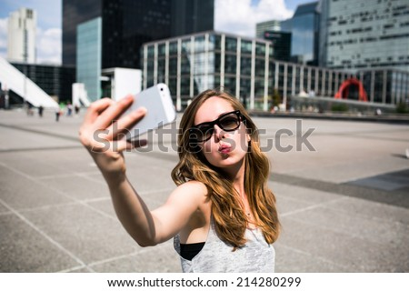 Beautiful young caucasian woman taking selfie self-portrait in Wall Street in New York while traveling across the USA - stock photo