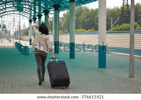 beautiful young Caucasian woman traveling pulling a luggage - stock photo