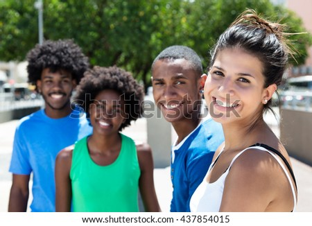 Beautiful young caucasian woman with african american friends in the city - stock photo