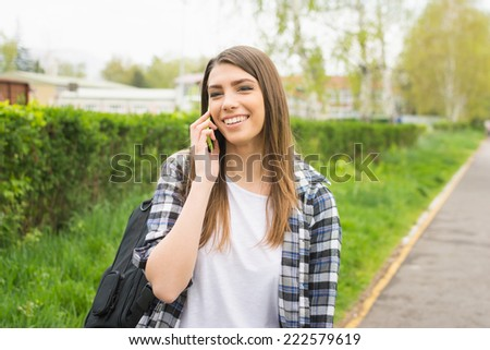 Beautiful young Caucasian woman with backpack speaking on the phone outdoors in park smiling. Cute teenage girl with checkered shirt and long blonde hair talking on smart phone. No retouch. - stock photo