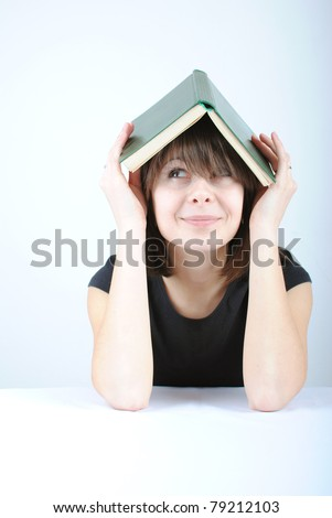 Beautiful young caucasian woman with book on her head, looking up - stock photo
