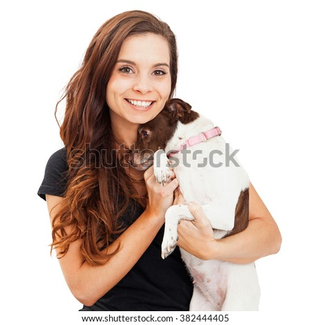 Beautiful young caucasian woman with brunette hair holding a shy little rescue dog that is hiding her head - stock photo