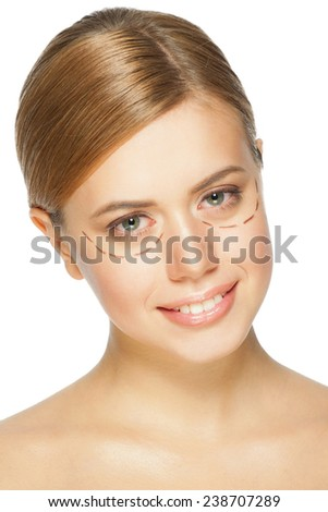 Beautiful young caucasian woman with perforation lines on her face before plastic surgery operation. Beautician touching woman face. - stock photo