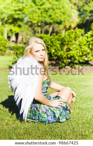 Beautiful young celestial angel in white wings seated on the grass looking back over her shoulder at the camera with a gentle expression - stock photo