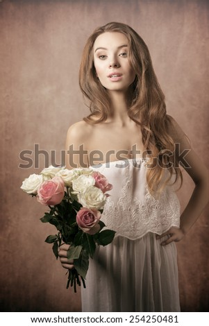 Beautiful, young, charming, gorgeous girl with curly hairstyle and bouquet of roses. She wears white old fashion dress. - stock photo