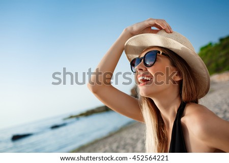 Beautiful young cheerful girl in hat and sunglasses rests at morning beach