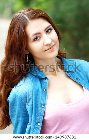 Beautiful young cheerful teenage girl in jeans jacket looking to the camera outdoors - stock photo