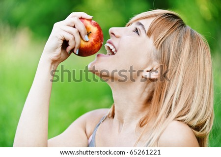 Beautiful young cheerful woman has turned in profile and bites red big apple, against green summer garden. - stock photo