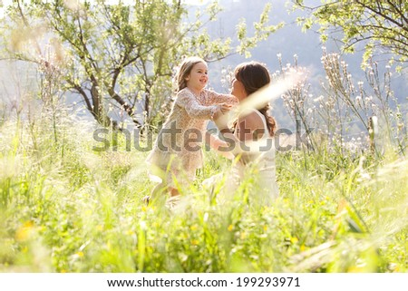 Beautiful young child girl approaching her mother with extended arms while in a dreamy holiday garden with bright sunshine. Family enjoying time together and being close, outdoors. - stock photo