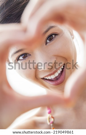 Beautiful young Chinese Asian woman girl smiling, making and looking through a hand heart shaped finger frame  - stock photo